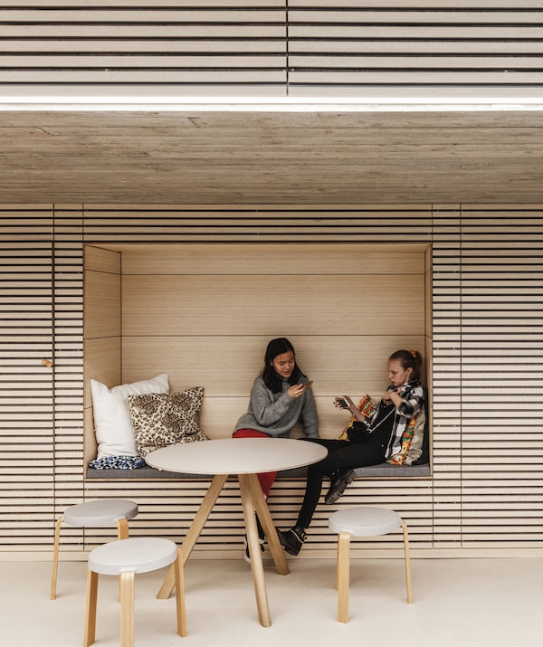 Two women sit in an alcove in a wall made of wooden planks, behind a table and chairs.