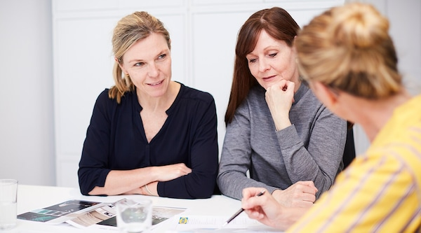 Two women sitting at a table with an IKEA kitchen planner.