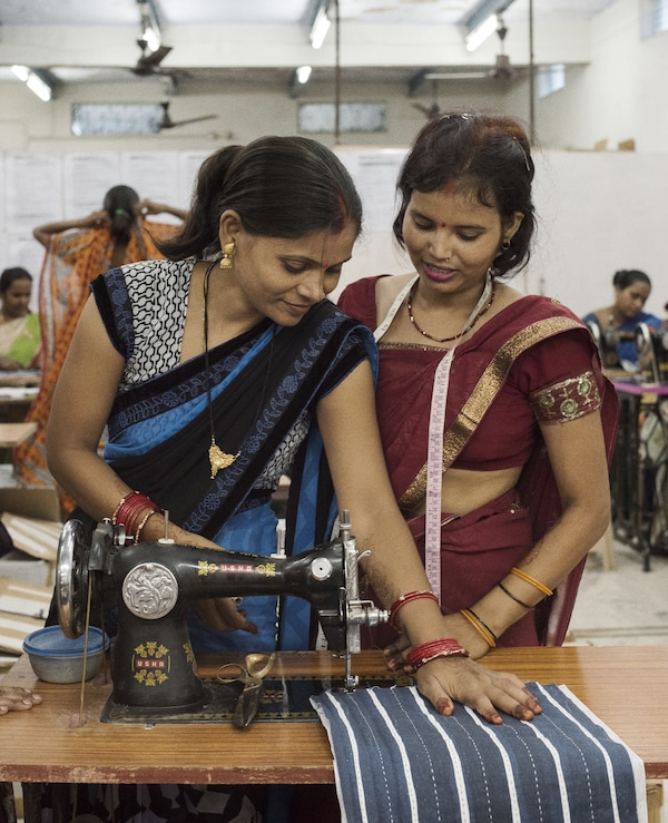 Two women working at a sewing machine.