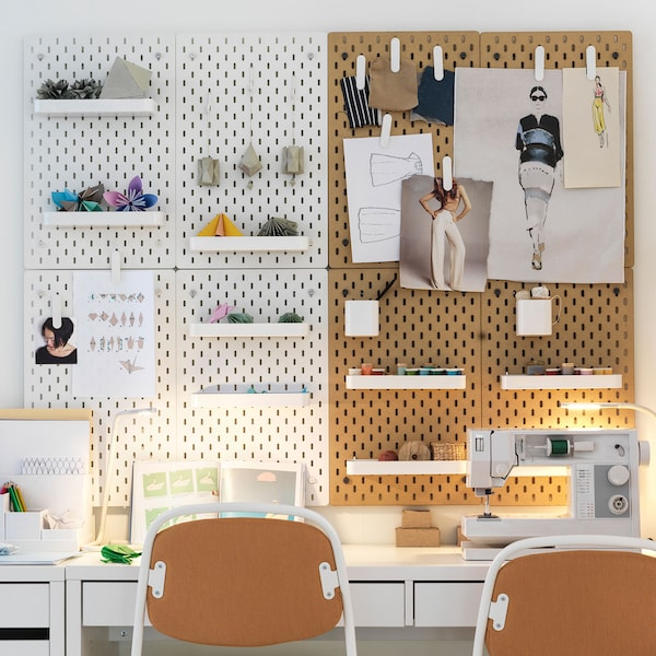 Two wood pegboards, one beige, one white, above a white desk set up for two people.