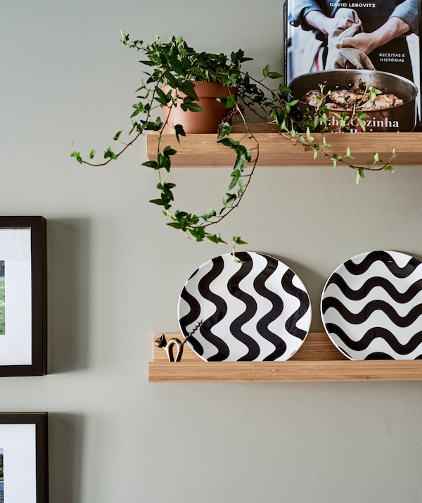 Two wood picture ledges, the bottom shelf has white plates with a wavy black pattern, the top has potted ivy and a cookbook.