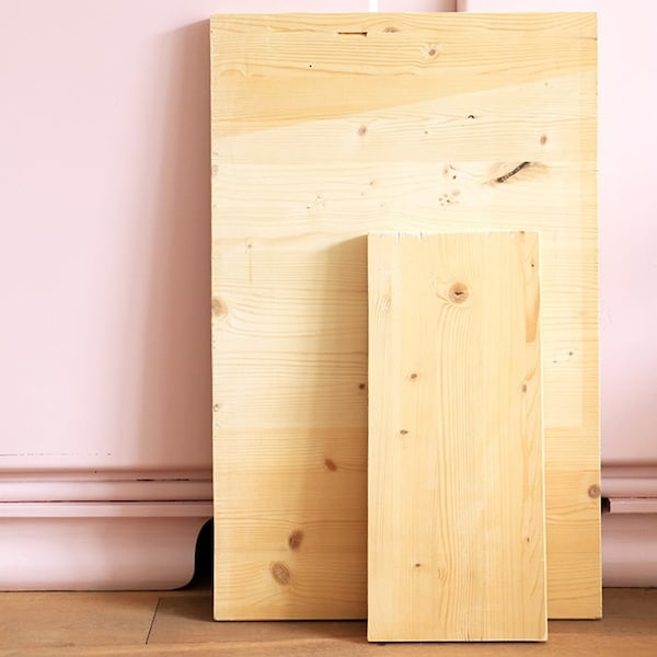 Two wooden planks against a pink wall