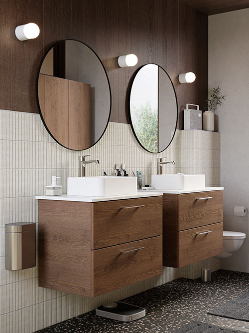 Two wooden sink cabinets, two large round mirrors, three wall lamps on the wall, beige tiles, dark terrazzo flooring.