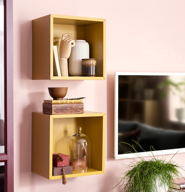 Two yellow, wall-hung, open EKET storage units with compositions of ceramic vases, wooden shapes, books and decorative boxes.