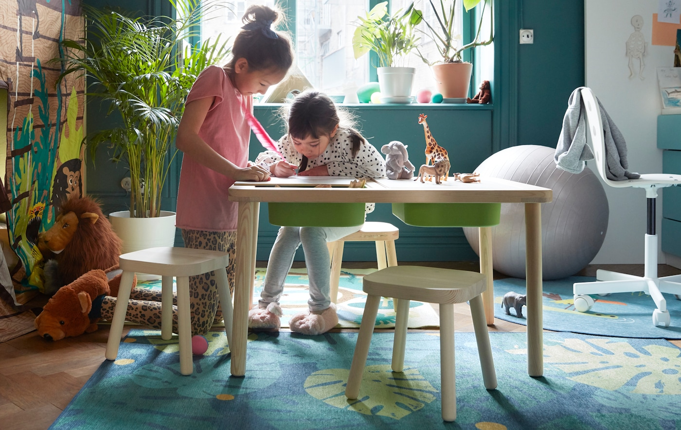 Two young girls doing crafts on a FLISAT children's table