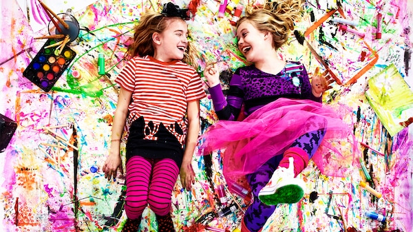 Two young girls laying on a colorful painted cloth with nearby paints.