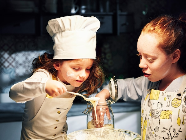 Two young girls pouring batter, with flour on their faces.