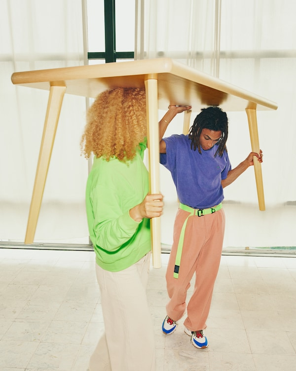 Two young people carrying the MARKERAD table above their heads.