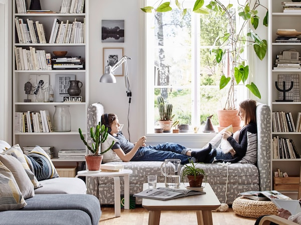 Two young people sitting across from each other on a sofa seat in a living room with tall bookcases.