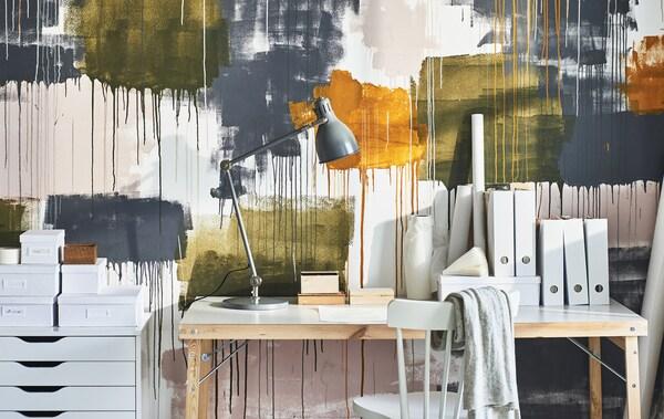 Työpöytä, laatikosto ja pinnatuoli kodin työpisteellä, jonka taustalla seinä ka on koristettu suurilla väriroiskeilla erivärisiä maaleja.