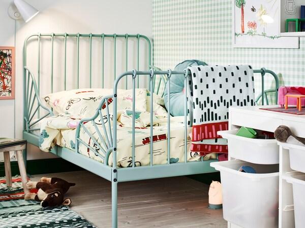 Tyrkysová posteľ MINNEN s nastaviteľnou dĺžkou v rohu detskej izby s hračkami, svetlom na čítanie a úložnými priestormi.