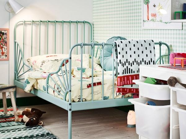 Tyrkysové prodloužitelná postel MINNEN v dětském pokoji, plném hraček. Na stěně je dětské osvětlení.