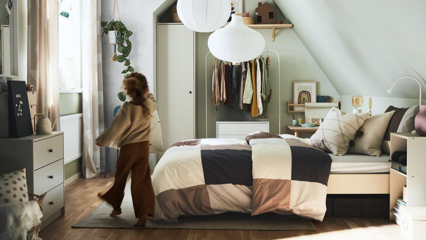Tyttö kävelee makuuhuoneeseen, jossa on sänky, jossa on ruskeat / harmaat ruudulliset liinavaatteet, sekä erilaisia säilytysratkaisuja.