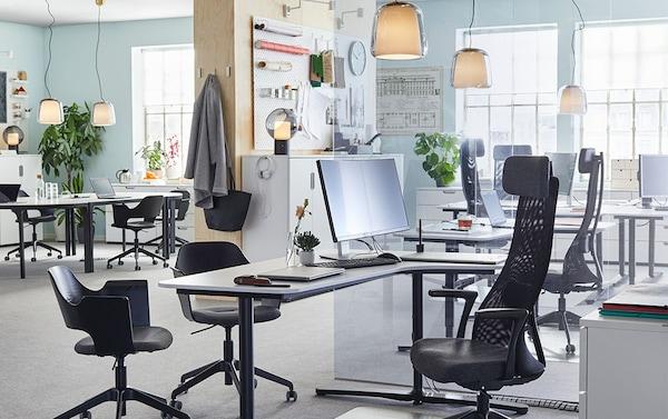 Tyylikkäät IKEA EVEDAL kattovalaisimet sopivat yhtä hyvin toimistoon kuin kotiinkin. Kuvassa myös valkoinen BEKANT sähkösäädettävä kulmapöytä, jossa on mustat jalat. Musta käsinojallinen työtuoli JÄRVFÄLLET ja mustaksi petsattu FJÄLLBERGET kokoustuoli.