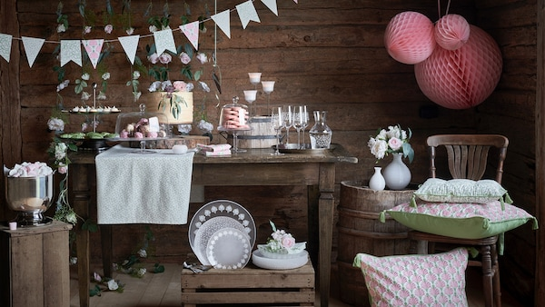 U štali se nalazi stol postavljen za zabavu s čašama, posuđem i ukrasima iz svečane INBJUDEN kolekcije.