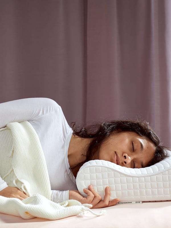 Ubrana w białą koszulkę kobieta o kasztanowych włosach śpiąca pod białym kocem, z głową na poduszce ergonomicznej ROSENSKÄRM.