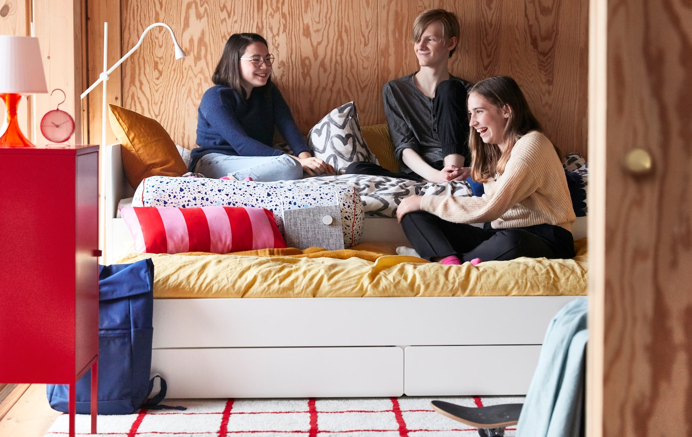 ウッドパネルのベッドルームで、ティーンエイジャーの仲間たちが、伸長式のSLÄKT/スレクト ベッドに集まって座り、お喋りしています。