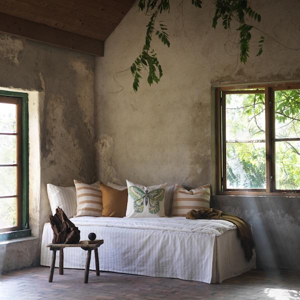 Udoban kutak s prozorima sadrži dnevni ležaj s prugastim braon jastučićima i RÖTFJÄRIL jastučićem s leptirom u sredini.