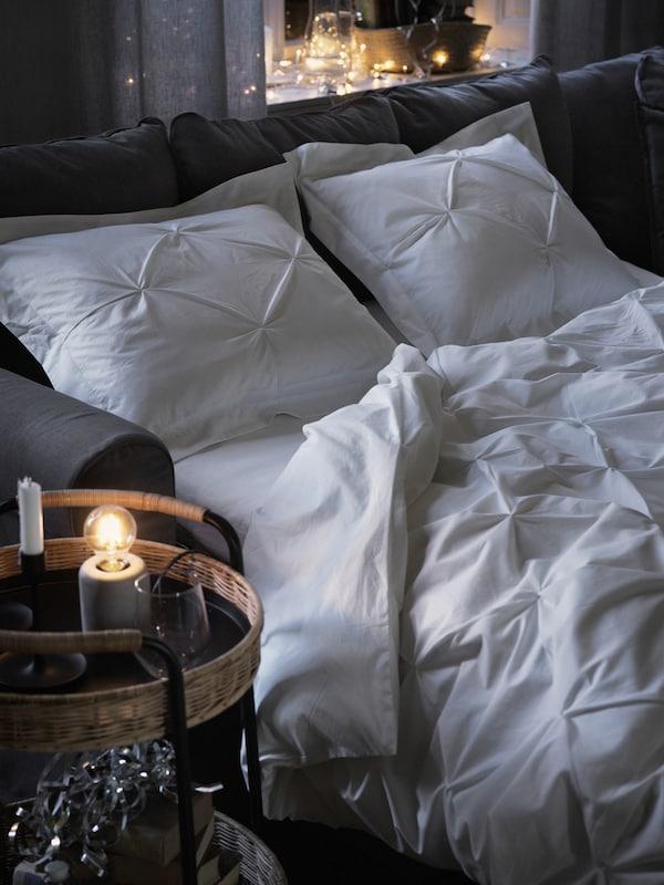 Udobna bela posteljina prekriva sivi GRÖNLID sofa ležaj, uz LUBBAN kolica od pruća odmah pored.