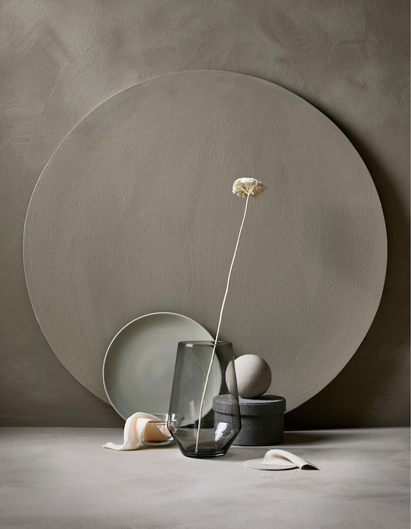 Udstilling med en glasvase og blomster, tallerken, opbevaringsboks og tekstiler i samme farver