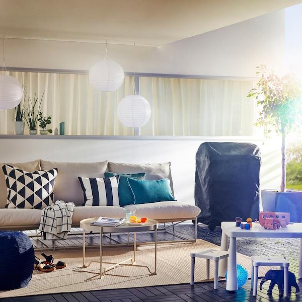 Überdachte Terrasse mit großem Sofa, Kindertisch, Kissen & Lampen für die ganze Familie.