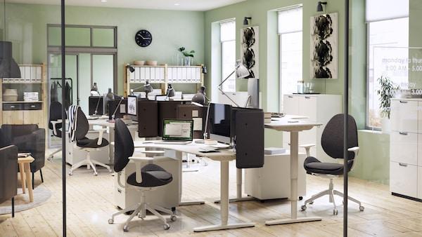 Ufficio dallo stile moderno con pareti in verde chiaro, scrivanie angolari BEKANT, regolabili in altezza, e sedie.
