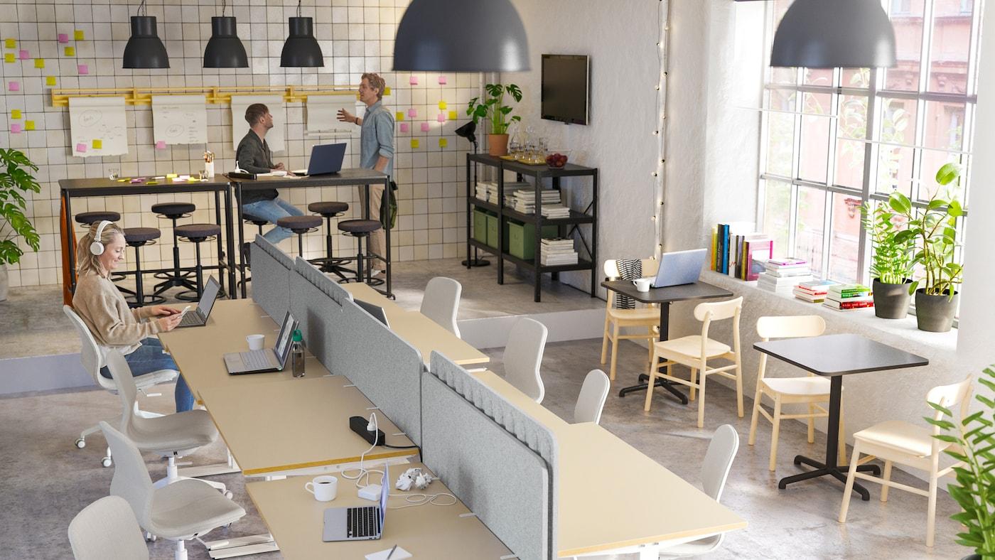 Ufficio open space con due uomini che lavorano accanto a scrivanie alte e una donna seduta su una sedia beige/bianca che scrive e-mail.