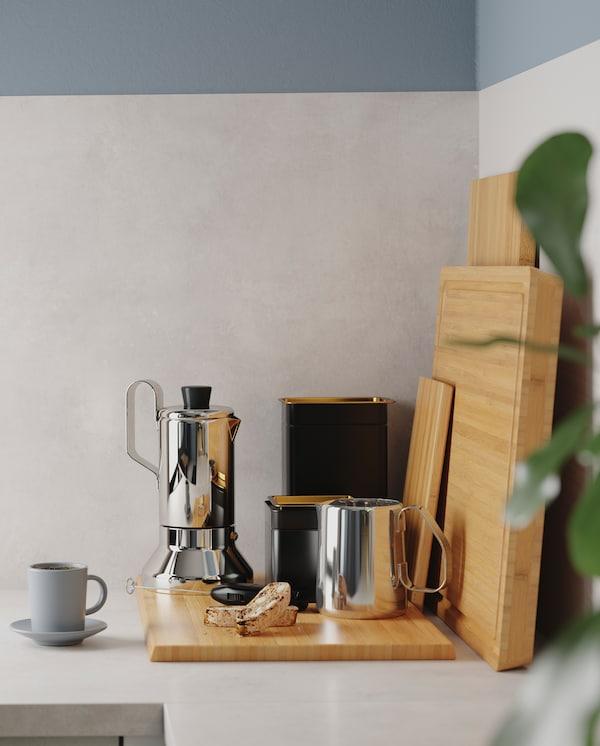 Ugao kuhinjske radne ploče s daskom za seckanje od bambusa, aparat za espreso od nerđajućeg čelika i dve crne konzerve za kafu.
