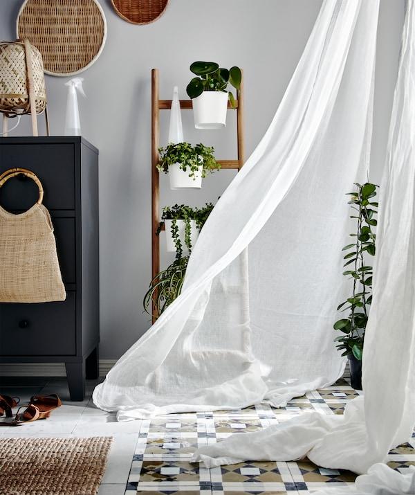Ugao prostorije, biljke pored prozora od poda do plafona s providnim zavesama u prvom planu, koje se talasaju pod naletom vetra.