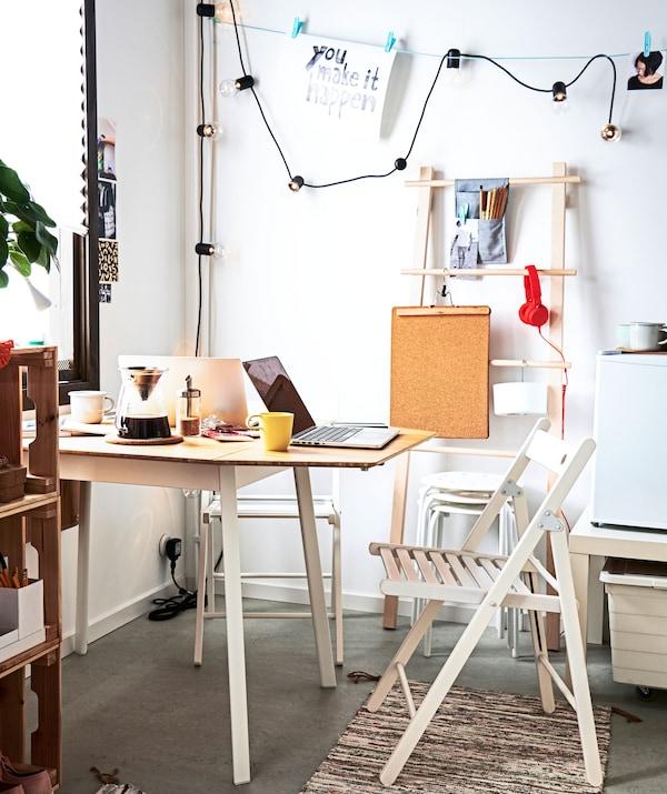 Ugao prostorije sa stolom, jedan kraj do zida, okružen sklopivim stolicama, dodatnim stoličicama i raznim elementima za odlaganje.