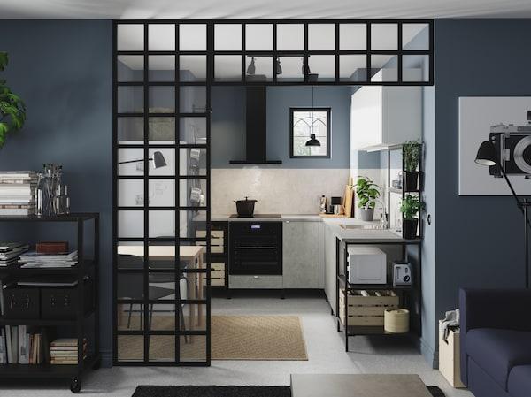Ugaona kuhinja u antracitu/ imitaciji betona/ beloj boji s otvorenim i zatvorenim elementima za odlaganje, crne lampe, bljke u saksijama i tepih od jute.