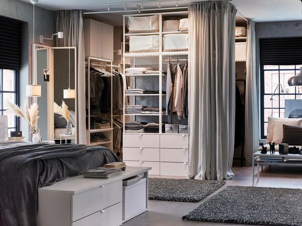 Uglavnom bela i siva spavaća soba s belim krevetnim okvirom, otvorenim garderoberom, svetlosivim zavesama i tamnosivim tepisima.