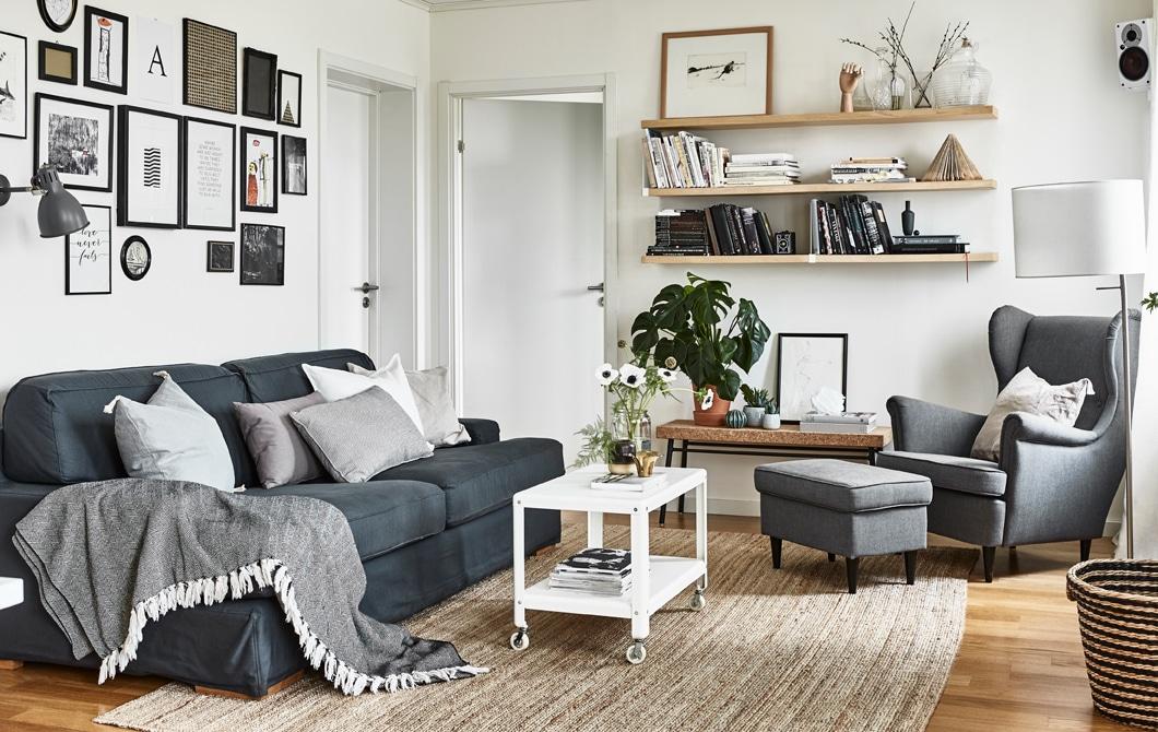 Ujęcie pokoju dziennego w neutralnych kolorach z sofą, fotelem i półkami.