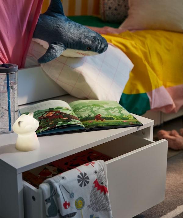 Úložný priestor pod posteľ na kolieskach vysunutý spod stola. Na stole je nočné svetlo, kniha a fľaša s vodou.