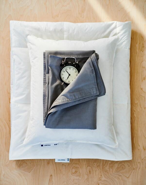 Ułożona na jasnym, drewnianym blacie złożona w kostkę biała kołdra z białą poduszką, ciemnoniebieskim prześcieradłem i staromodnym, czarnym budzikiem.