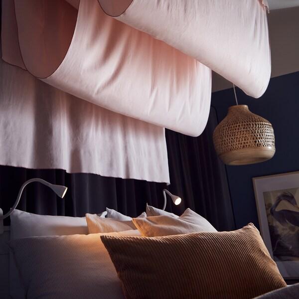 Ułożone w fałdy różowe zasłony MOALISA zwisające z sufitu nad łóżkiem z ciemnobeżową poduszką. Obok wisi lampa wisząca z bambusowym kloszem.