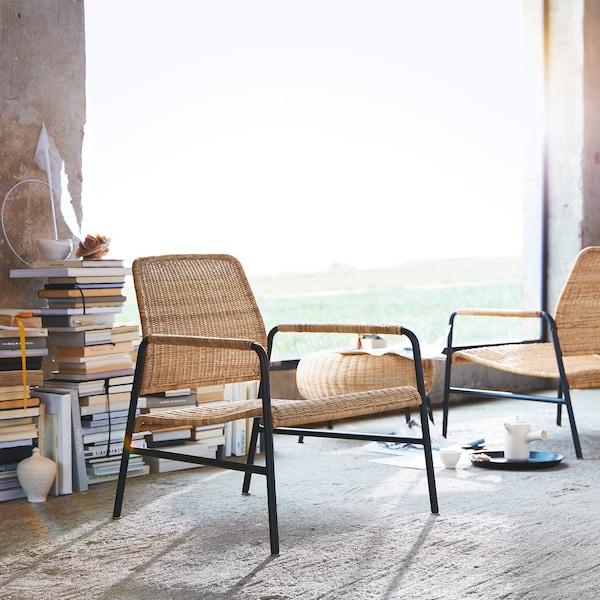 두 개의 ULRIKSBERG 울릭스베리 암체어가 커다란 창문 앞에 있어요. 검은색 금속 프레임과 손으로 짠 라탄 시트와 등받이가 있는 의자랍니다.
