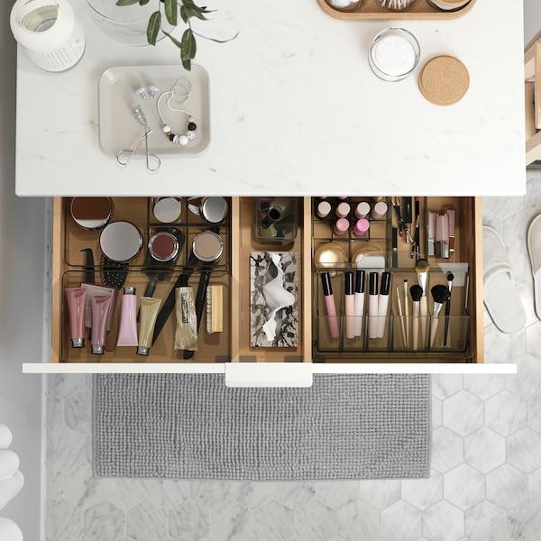 Um armário com lavatório com uma bancada com efeito mármore. Uma das gavetas aberta e no seu interior estão caixas GODMORGON que ajudam a organizar a maquilhagem.