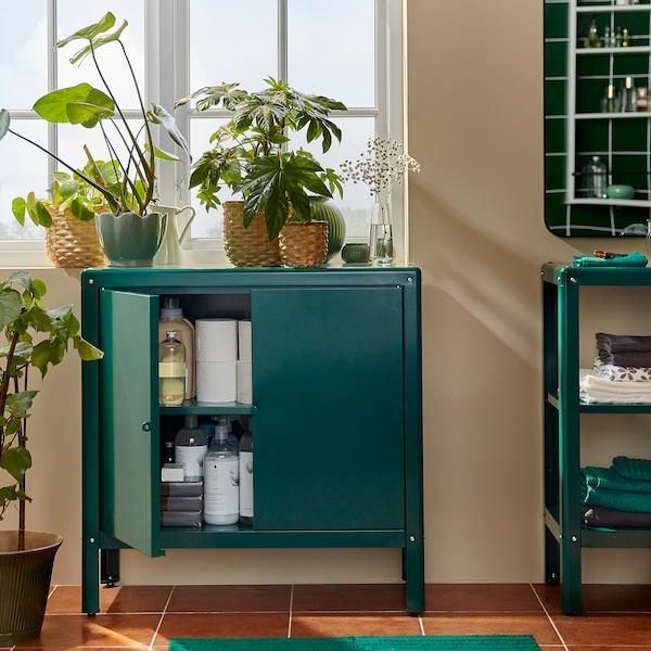Um armário KOLBJÖRN em verde em frente a uma janela. Uma das portas aberta, com papel higiénico e detergentes arrumados no interior.