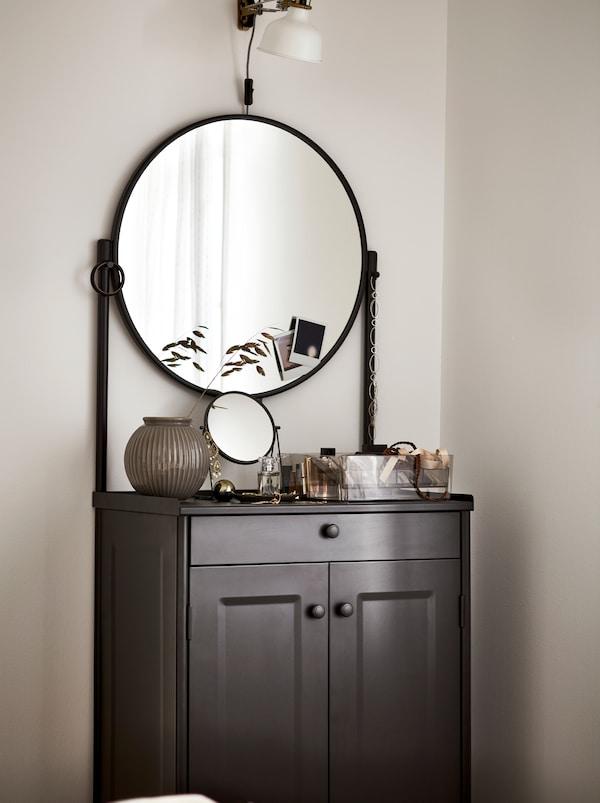 Um armário KORNSJÖ em preto com um grande espelho redondo, com objetos decorativos expostos, por cima do qual está um candeeiro branco.