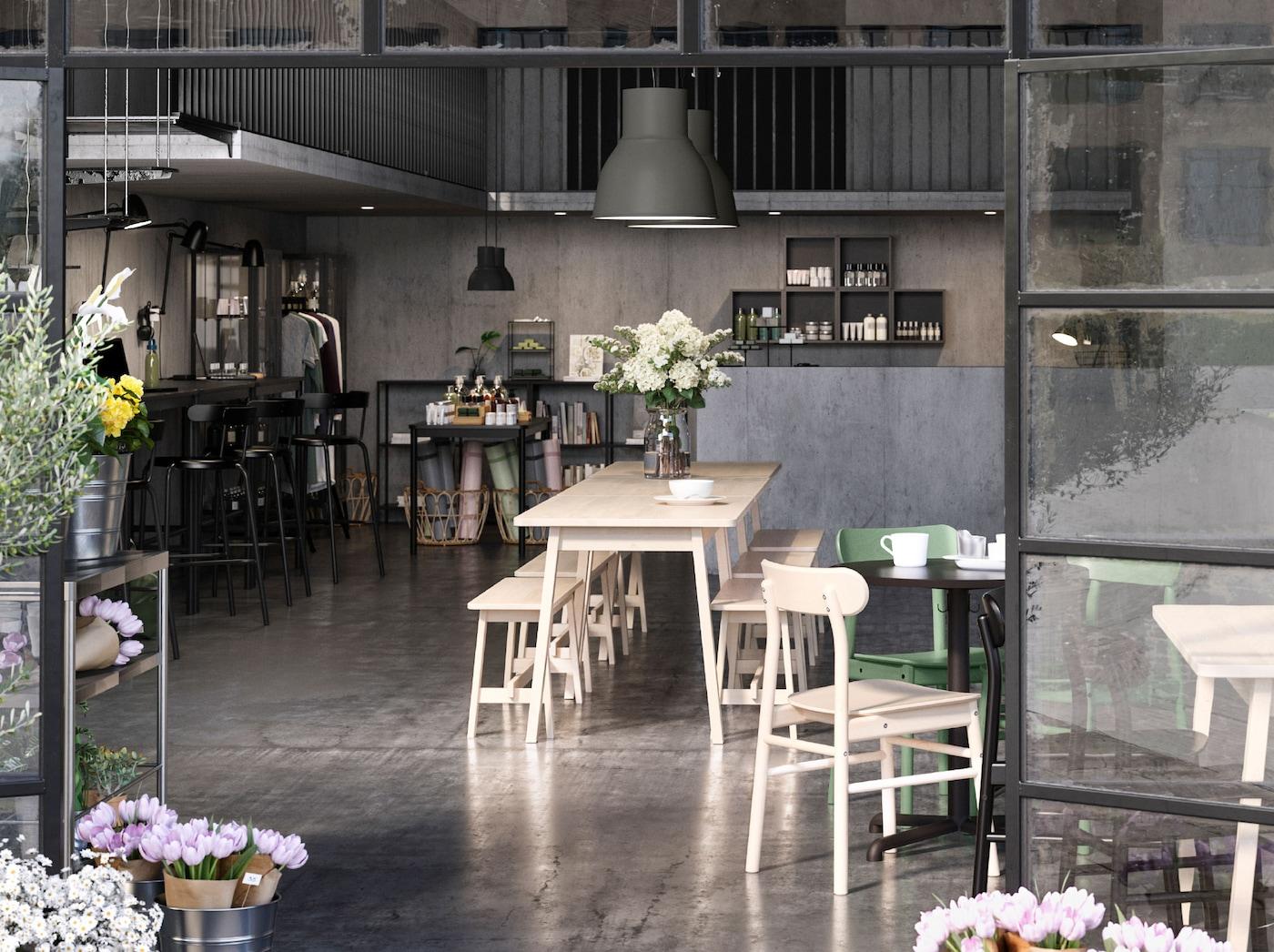Um café, loja e espaço de coworking em plano aberto, enquadrado por duas portas envidraçadas abertas. Flores na mesa e junto às portas.