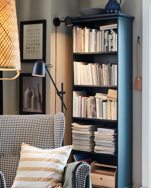 Um canto de leitura acolhedor com um candeeiro de parede SKURUP, um candeeiro de pé SKURUP, uma poltrona e uma estante em azul esverdeado escuro.