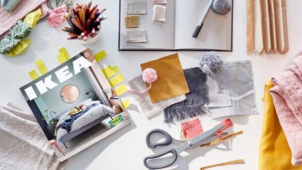 Um Catálogo IKEA 2021, um caderno para anotar ideias, uma tesoura e retalhos de tecido em cores pastel e amarelo mostarda.