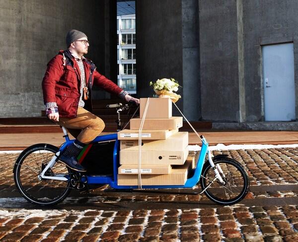 Um cliente a transportar embalagens planas numa bicicleta comprida num passeio em calçada de pedra.