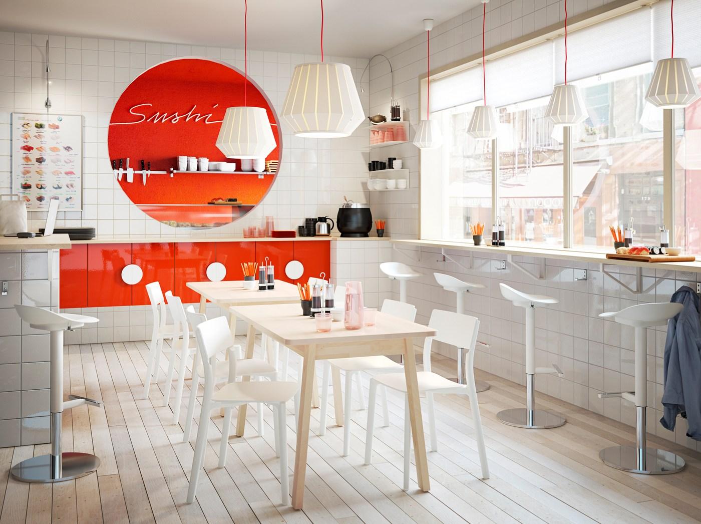 Um colorido restaurante de sushi, em branco e laranja, com bancos altos e cadeiras baixas da gama JANINGE, em branco.
