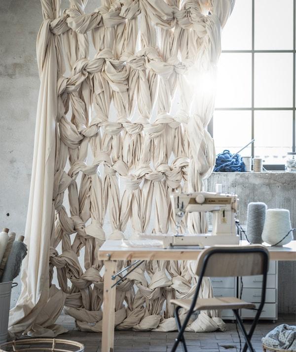 Um cortinado em macramé pendurado atrás de uma mesa com uma máquina de costura em cima.