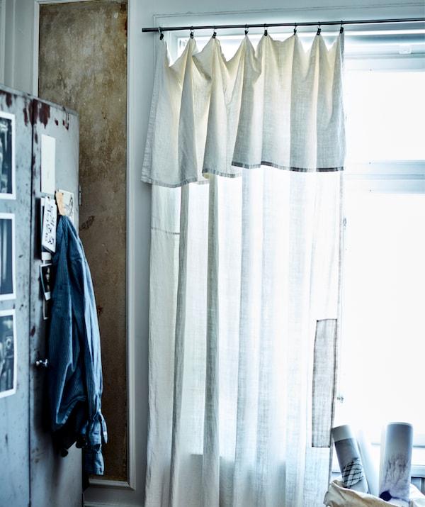 Um cortinado transparente pendurado numa janela ao lado de um armário em metal.