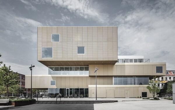 Um edifício grande com o formato de blocos sobrepostos e coberto por metal dourado.