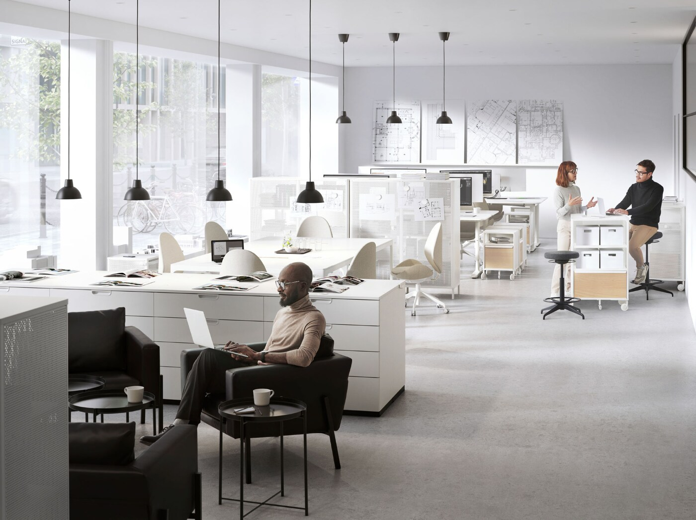Um escritório em open space com duas áreas informais. Um homem a trabalhar numa poltrona KOARP e duas pessoas a conversar junto a uma estante BEKANT.