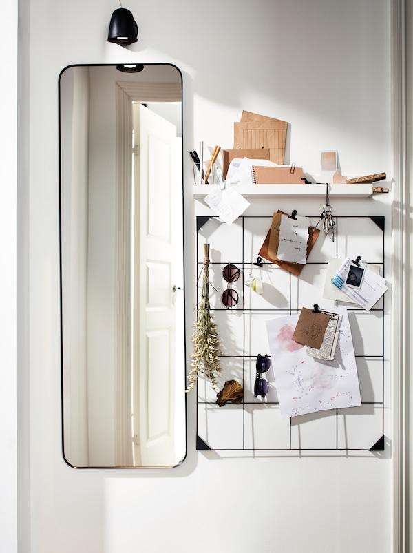 Um espelho LINDBYN alto, um quadro para mensagens SÖSDALA em aço preto com molas e uma prateleira, com notas e óculos de sol.